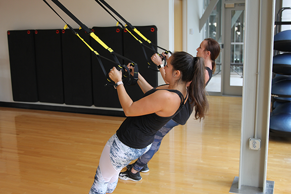 Two women exercise with TRX straps at Rec & Wellness Center.